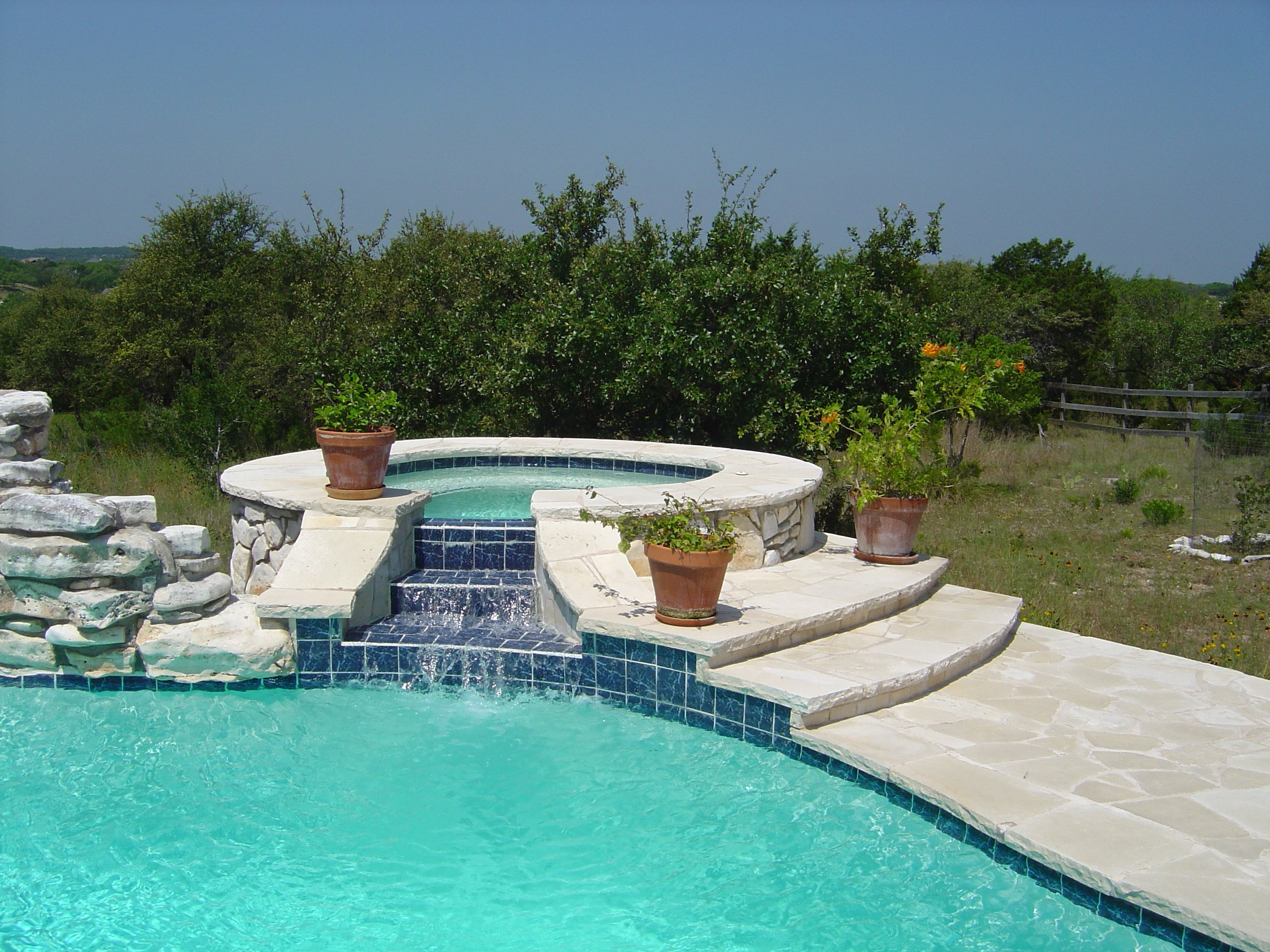Free Form Raised Limestone Spa with Tiered Spillway
